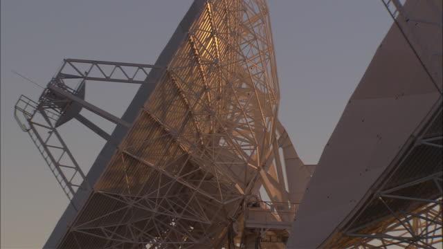 two radio telescopes rotate in unison. - astronomiskt teleskop bildbanksvideor och videomaterial från bakom kulisserna