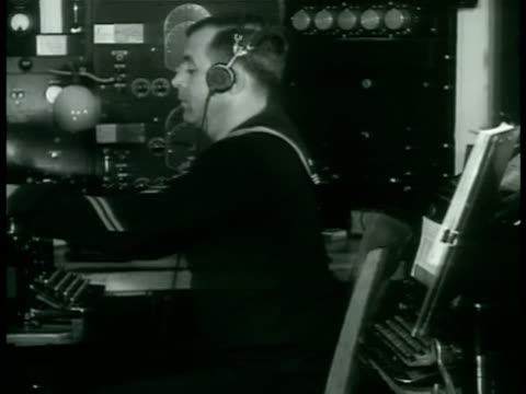Two radiomen working in radio room w/ headsets typewriters Radioman using teletype VS Dispatcher standing marking on Dispatch Board wall CU listing...