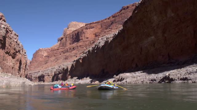 ws two rafts floating on river and red cliffs on both sides / grand canyon, arizona, usa - grand canyon stock videos & royalty-free footage
