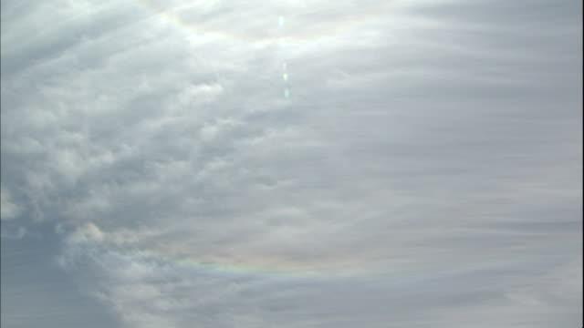 vídeos de stock, filmes e b-roll de two rainbow halos encircle a sunburst on a cloudy day. - parélio