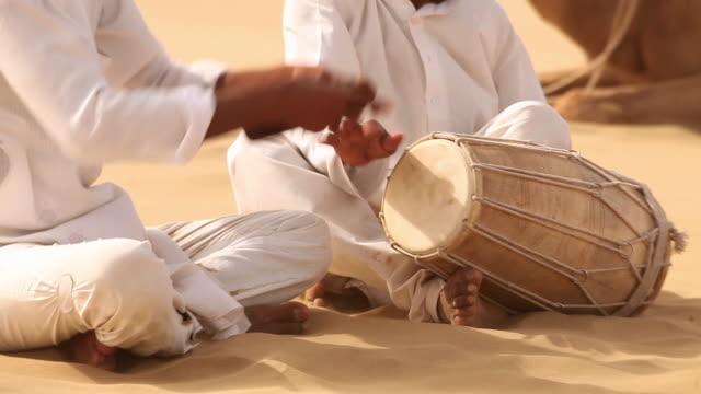 Two rajasthani men playing traditional musical instrument on desert, Sam Desert, Jaisalmer, Rajasthan, India