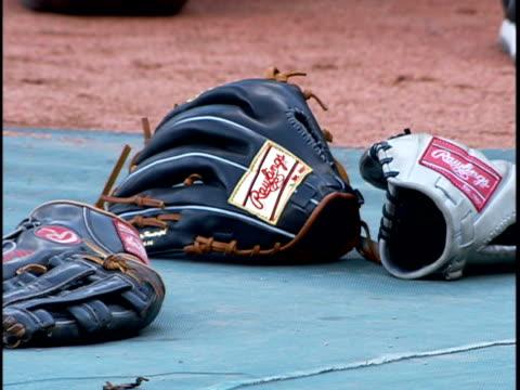 vídeos y material grabado en eventos de stock de two rawlings baseball gloves on sheet on floor various unidentifiable baseball player's feet stepping in out of frame bg fg sports practice - guante de béisbol