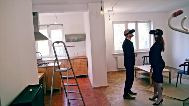 vídeos y material grabado en eventos de stock de dos agentes inmobiliarios utilizando auriculares vr - realidad aumentada