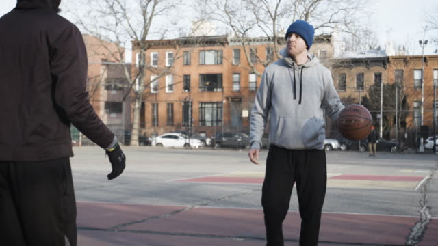 Two real people in their twenties play basketball on a cold Brooklyn, NYC morning - 4k