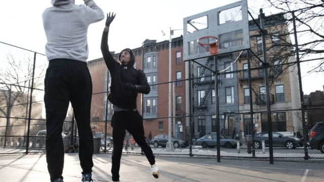 Two real people play basketball on a cold, Brooklyn, NYC morning - slow motion - 4k