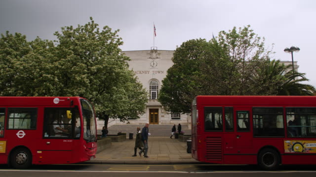 vidéos et rushes de two red busses stop in front of hackney town hall, london - hackney