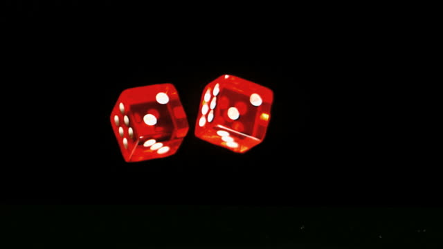 Two red dice falling and bouncing close up on black background