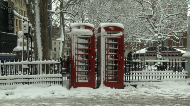 WS PAN Two red telephone booths covered in snow in Leicester Square, London, United Kingdom