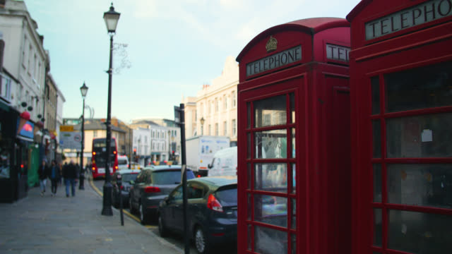two red telephone boxes on greenwich church street, london - 電話ボックス点の映像素材/bロール