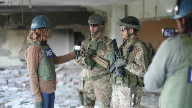 zwei reporter im kriegsgebiet - war stock-videos und b-roll-filmmaterial