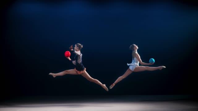 slo mo ld zwei rhythmische turnerinnen bewegen sich in entgegengesetzte richtungen und fangen ihre ***, während sie einen split-sprung durchführen - akrobat stock-videos und b-roll-filmmaterial