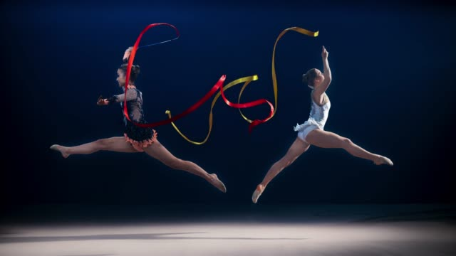 slo mo ld two rhythmic gymnasts moving in opposite directions and performing a split leap while swirling ribbons - rhythmic gymnastics stock videos & royalty-free footage