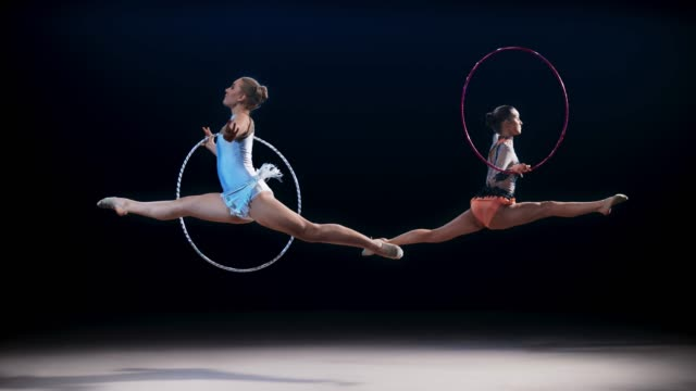 slo mo ld two rhythmic gymnasts moving in opposite directions and performing a split leap with hoops - rhythmic gymnastics stock videos & royalty-free footage