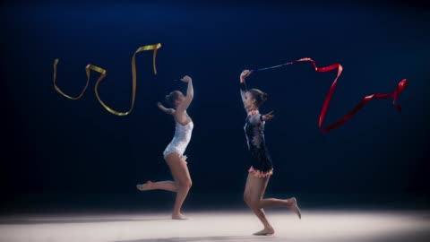 vidéos et rushes de slo mo speed ramp ld deux gymnastes rythmiques se déplaçant dans des directions opposées et effectuant un saut fractionné tout en tourbillonnant des rubans - représentation artistique
