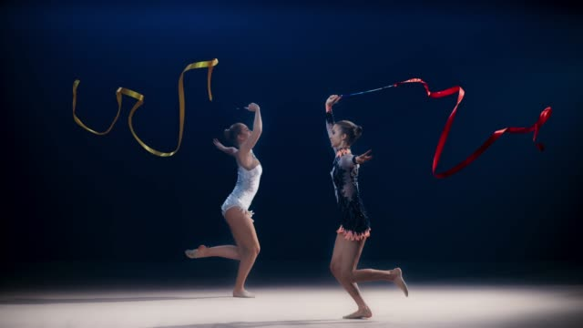 vídeos de stock e filmes b-roll de slo mo speed ramp ld two rhythmic gymnasts moving in opposite directions and performing a split leap while swirling ribbons - perfeição