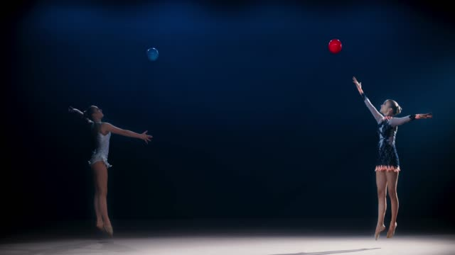 slo mo ld two rhythmic gymnasts moving in opposite directions and throwing their balls high in the air - performing arts event stock videos & royalty-free footage