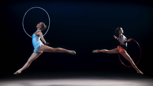 slo mo speed ramp ld two rhythmic gymnasts moving opposite each other doing a split leap with a hoop - gymnastics stock videos & royalty-free footage