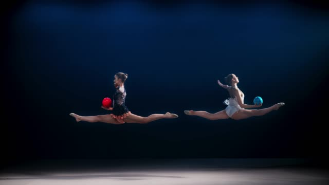 slo mo two rhythmic gymnasts opposite each other doing a split leap while throwing their balls into the air - lanciare video stock e b–roll