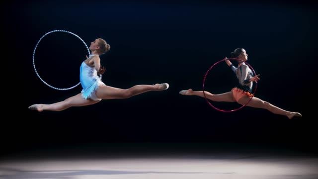vídeos de stock, filmes e b-roll de slo mo dois ginastas rítmicos oposto uns aos outros fazendo um salto dividido com um aro - acrobata
