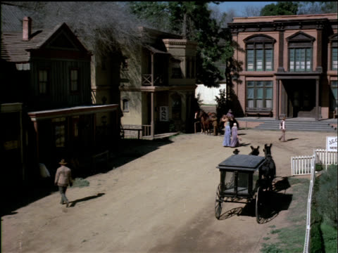 vídeos de stock e filmes b-roll de two riders mount their horses and gallop out of an old western town. - cultura americana