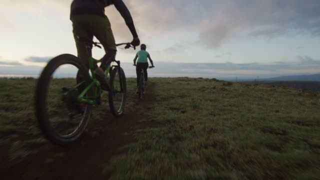 stockvideo's en b-roll-footage met twee renners (een vrouw en een mannetje) mountainbike in de rocky mountains ten westen van denver, colorado bij zonsopgang - sporthelm