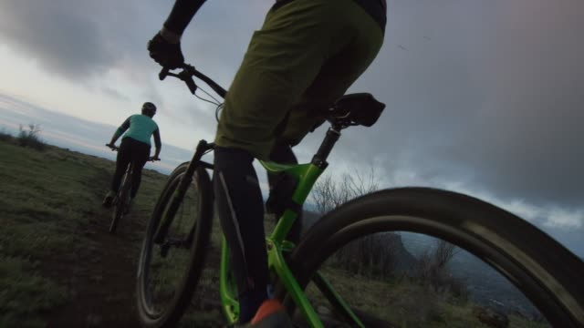 two riders (a female and a male) mountain bike in the rocky mountains west of denver, colorado at sunrise - gara off road video stock e b–roll