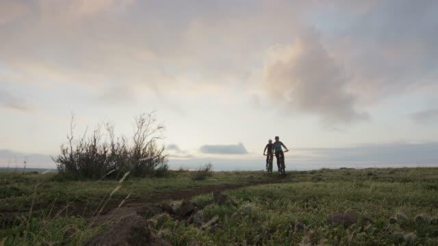 två ryttare (en kvinnlig och en manlig) mountainbike i klippiga bergen väster om denver, colorado vid sunrise - partire bildbanksvideor och videomaterial från bakom kulisserna