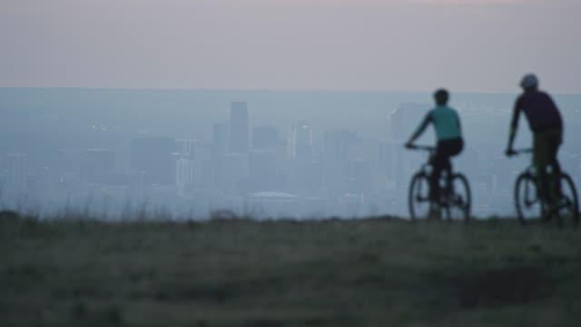 zwei reiter (ein weibchen und ein mann) mountainbike in den rocky mountains west von denver, colorado mit der city below bei sunrise - boulder stock-videos und b-roll-filmmaterial