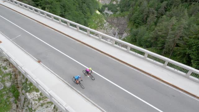 aerial two road cyclists on a bridge high above a gorge in the mountains - coppia di adulti di mezza età video stock e b–roll