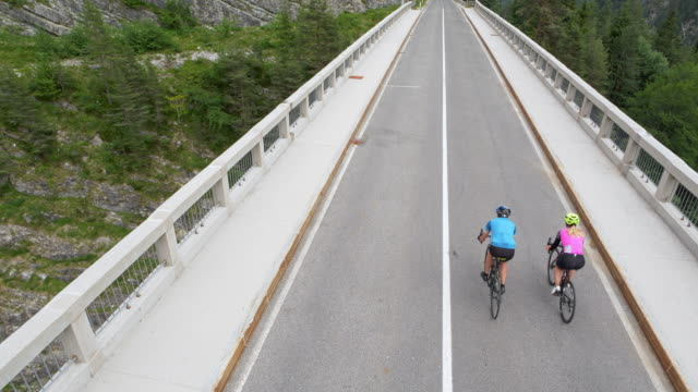 aerial two road cyclists riding across a bridge in the mountains - road marking stock videos & royalty-free footage