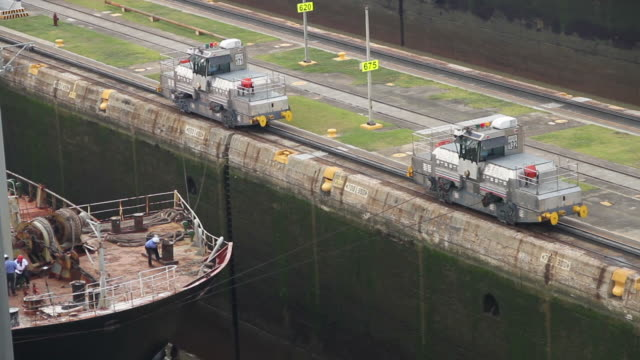 two robot trains pull a ship into the panama canal - panamakanal stock-videos und b-roll-filmmaterial