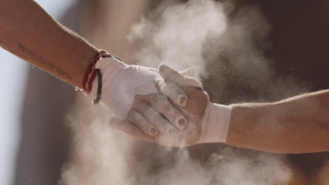 CU SLO MO. Two rock climbers slap hands together in a cloud of chalk dust.
