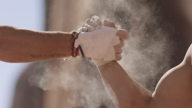 vídeos de stock e filmes b-roll de cu slo mo. two rock climbers slap hands together in a cloud of chalk dust. - apoio