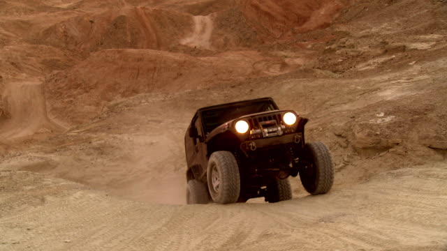 ws zo zi two rock crawlers with their all terrain vehicles moving in mountainous desert area at dusk / salton city, california, usa  - off road car stock videos and b-roll footage