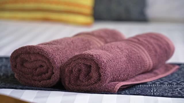 zwei aufgerollte rosa badetücher auf bettwäsche - b roll stock-videos und b-roll-filmmaterial