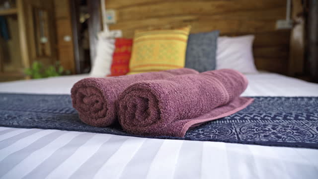 vídeos de stock e filmes b-roll de two rolled up pink bath towels on luxury hotel bed - b roll