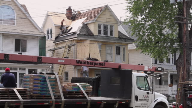 WS Two roofers working / Buffalo, New York, USA