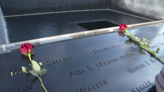two roses are placed on the wall at the 9/11 memorial site in lower manhattan in honor of the victims of the paris, france terrorist attacks. no audio - gedenkveranstaltung stock-videos und b-roll-filmmaterial