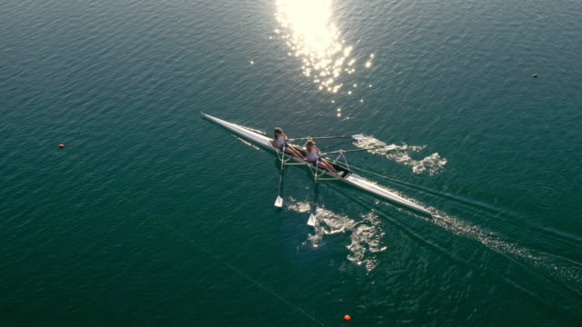 aerial two rowers sculling across a sunny lake in a double scull - rowing stock videos & royalty-free footage
