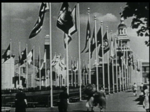 vídeos de stock, filmes e b-roll de two rows of blowing flags with buildings in background / avenue of states / ny world's fair - world's fair de nova york