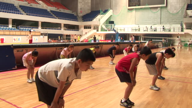 vidéos et rushes de ws two rows of children doing exercises on side of basketball court/ beijing, china - reportage