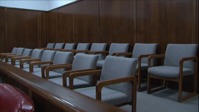 two rows of empty chairs occupy a courtroom. - court room stock videos & royalty-free footage