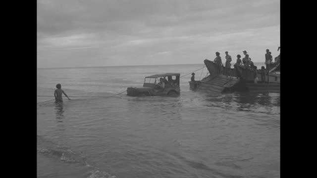 stockvideo's en b-roll-footage met two rows of new guinean natives wearing loincloths / catamarans moving out to sea / a schooner loaded with scores of waving us soldiers / the men... - rieten dak