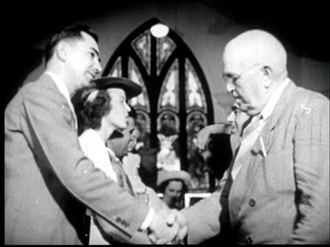 1945 ms two rows of people in church facing each other and shaking hands with gothic arch stained glass window in background/ sylacauga, alabama - congregation stock videos and b-roll footage
