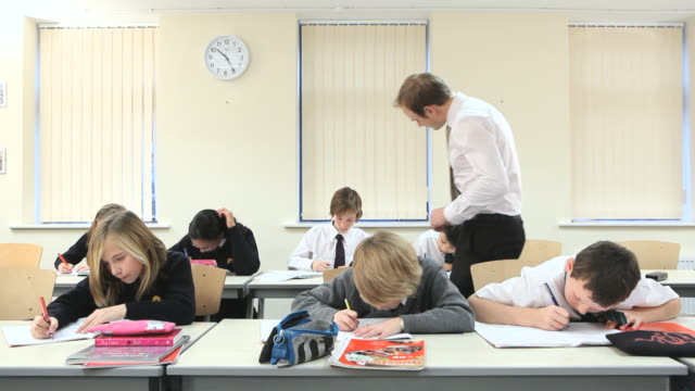 ws two rows of school children writing on paper, teacher walking between desks for checking work / bristol, united kingdom - klassenzimmer stock-videos und b-roll-filmmaterial