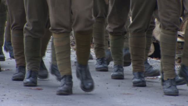 two rows of soldiers legs marching on paved walkway, calves in leg green wraps, puttees, black boots on feet, halting, stopping & starting, burlap... - marschieren stock-videos und b-roll-filmmaterial