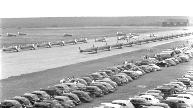 two rows of wwii trainer aircraft taxi toward an airfield as spectators watch from rows of parked cars. - out take stock videos & royalty-free footage