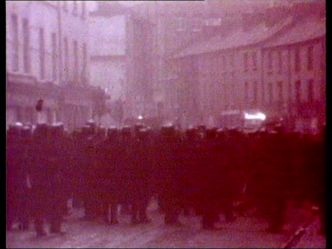 cbv two ruc officers in front of vehicle ext gv ruc landrover towards and past down road red tinted pictures gv line of officers in street as burning... - b rolle stock-videos und b-roll-filmmaterial