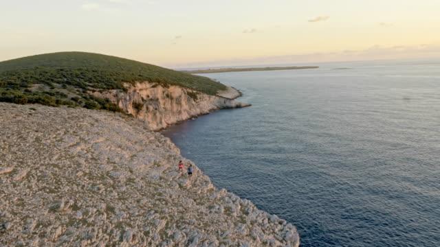 stockvideo's en b-roll-footage met luchtfoto twee lopers lopen in de buurt van de rand van de witte klif boven de zee bij zonsondergang - cres kroatië