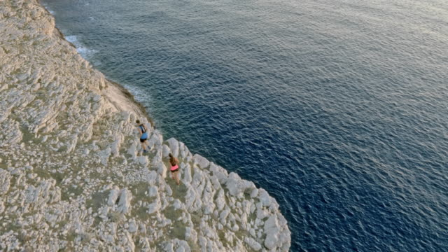 aerial two runners running on a white cliff rising from the sea in setting sun - vest stock videos and b-roll footage